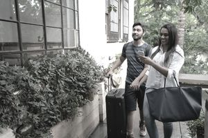 A smiling couple arrives with luggage outside the rustic Airbnb home where they will be paid guests
