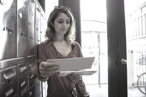 Young woman checking mailbox in apartment entrance.