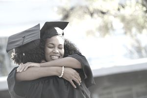 Two college graduates hugging