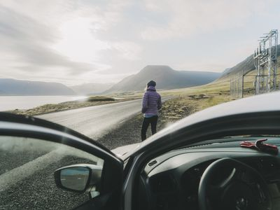 A woman looks out at a scenic landscape in front of her rental car