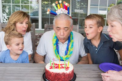 Senior man blowing out candles on birthday cake with family