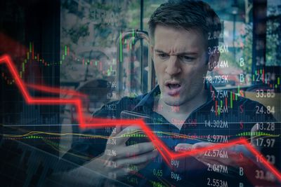 Upset looking man who is looking at his cell phone overlaid with red trend line heading downward and stock ticker symbols
