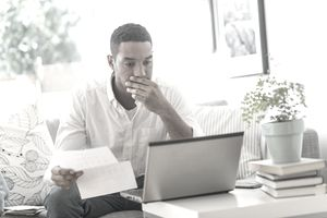 Young man reviews paperwork while using laptop at home