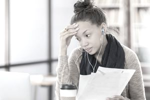 A worried college student has one hand on her forehead while holding papers and looking at a laptop, searching for a job