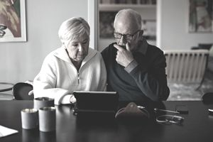 Senior couple using a digital tablet while sitting at a table in the living room
