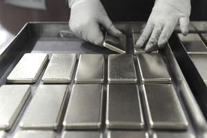 An employee arranges one kilogram gold bars at a mint refinery in Australia.