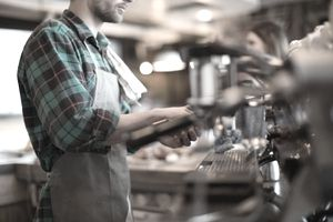 A barista working in a coffee shop where customers frequently make small transactions