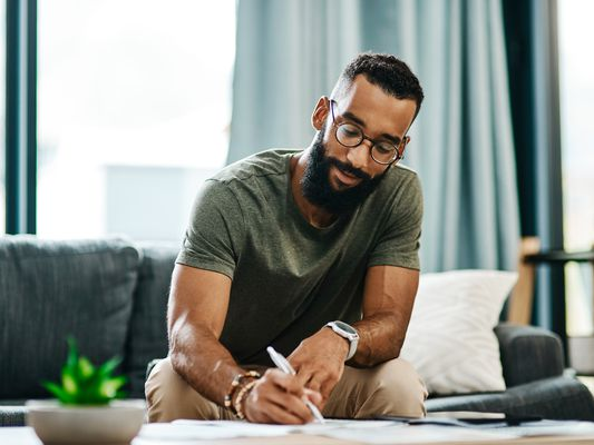 A bearded man with dark skin and glasses works at his coffee table