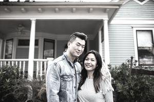 A young couple stand in front of their new home, which came with a good mortgage they were able to assume.