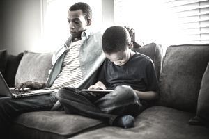 Divorced father sitting on sofa with son, studying his tax info on laptop as his son plays on tablet during his joint custody time