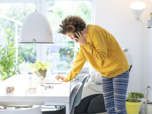 Woman using laptop and cell phone on table at home