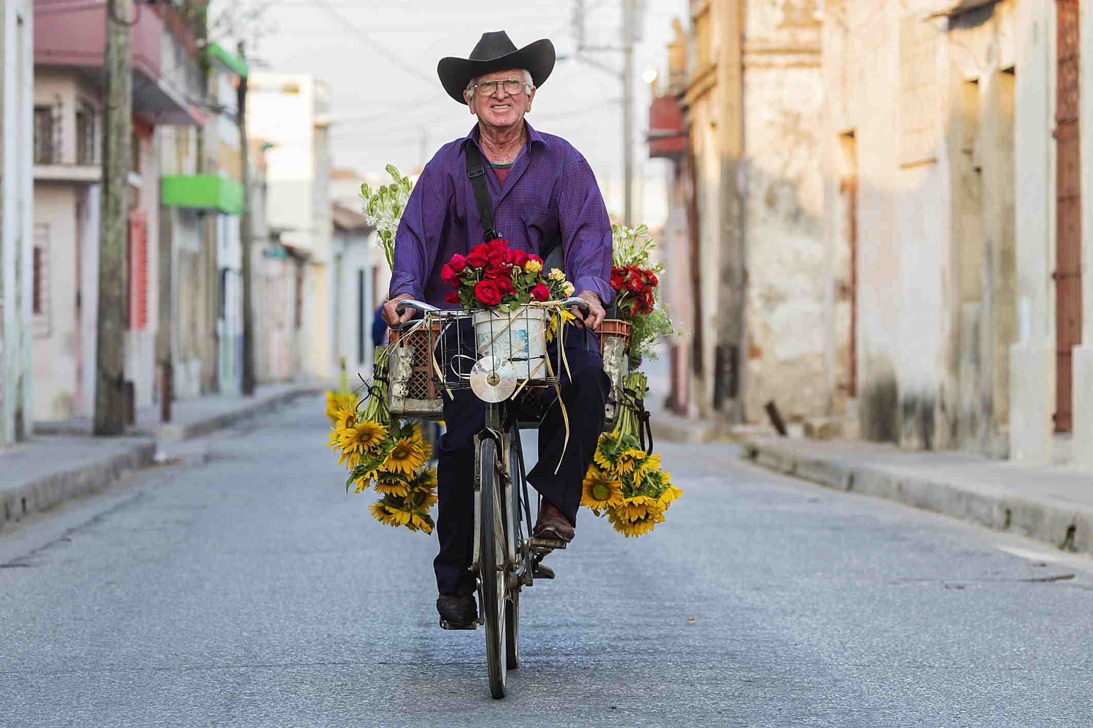 senior man riding a florist delivery bicycle