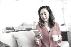 A woman is seated on a couch with her phone in one hand and a coffee mug in the other.