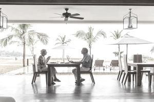 Elderly couple enjoying lunch within their timeshare resort with a tropical backdrop of palm trees
