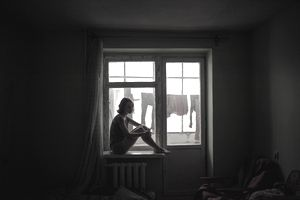 young person sitting in the silhouette of window