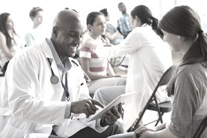 Doctor talking with patient in a room filled will medical providers and patients at a free clinic.