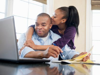 dad working on a laptop while daughter kisses and hugs him