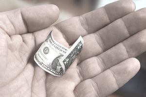 small dollar bill in man's hand
