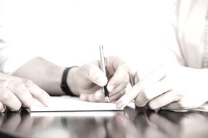 Close up of a person signing a warranty deed