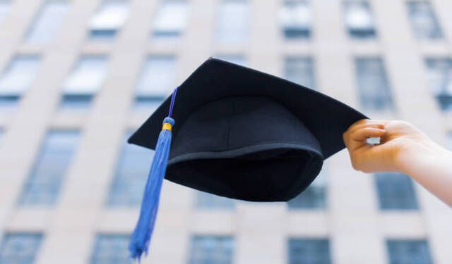 Image of a graduation hat raised in celebration due to receiving the gift of college