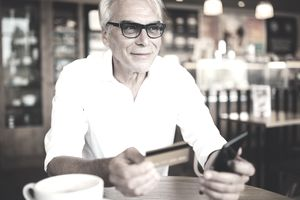 Senior man using smartphone and debit card