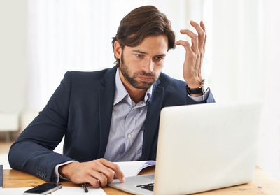 Distressed investor looking at a laptop