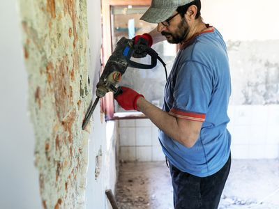 A construction worker uses an automatic hammer on a concrete and brick wall