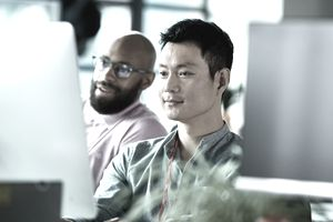 Two male co-workers looking at computer screen and concentrating