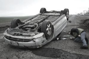 Man examining a rolled-over car