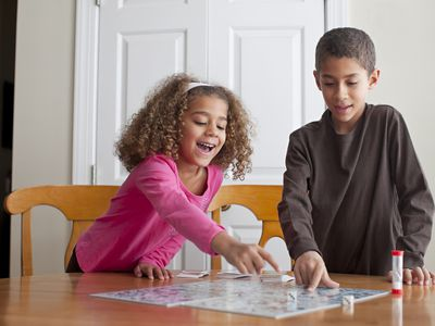 Mixed race children playing board game together