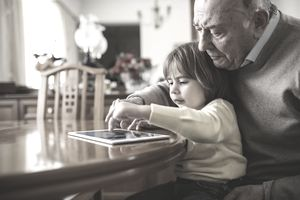 Grandfather and his grandson using a digital tablet