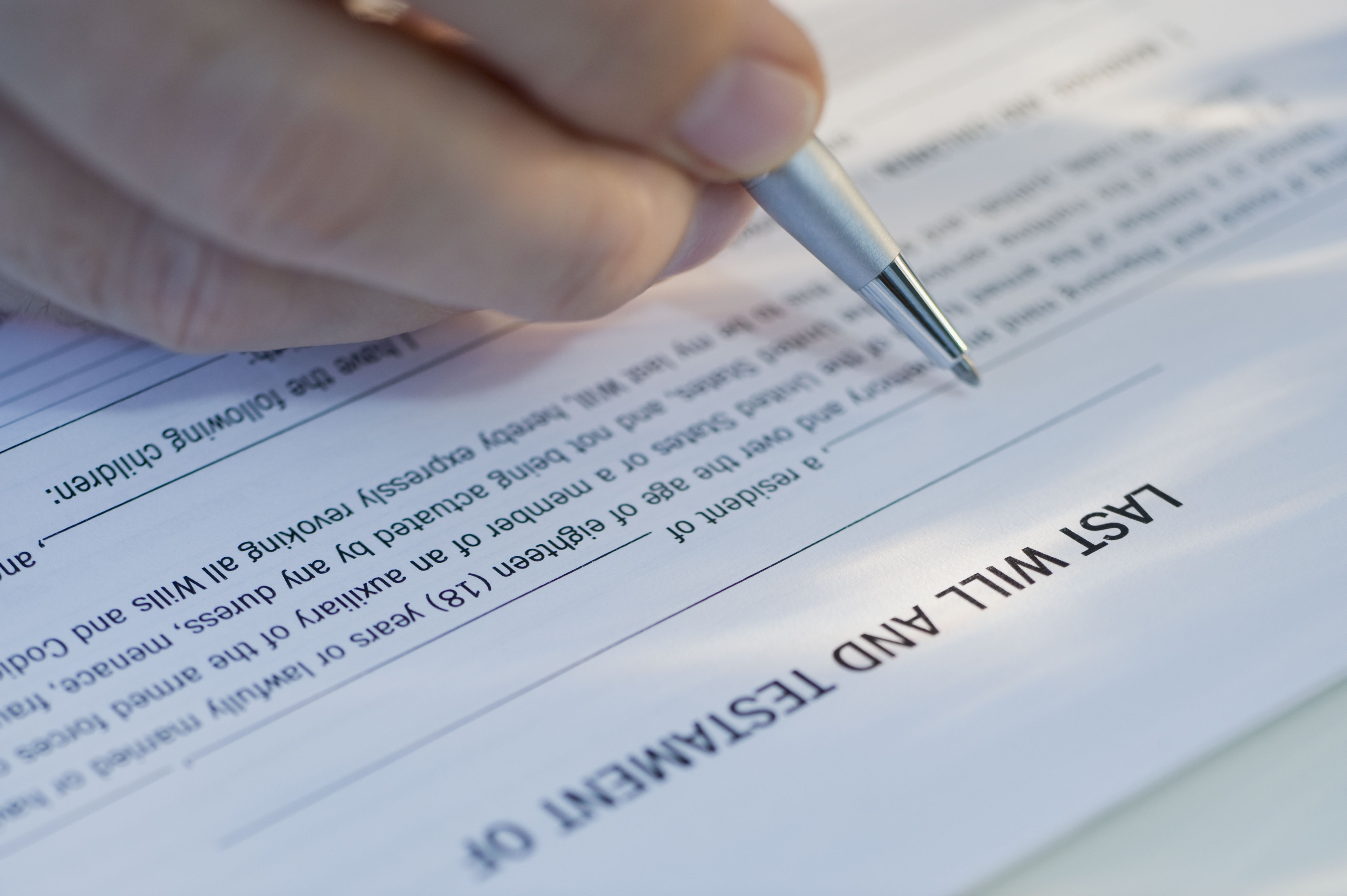 Closeup of a hand filling out a will form