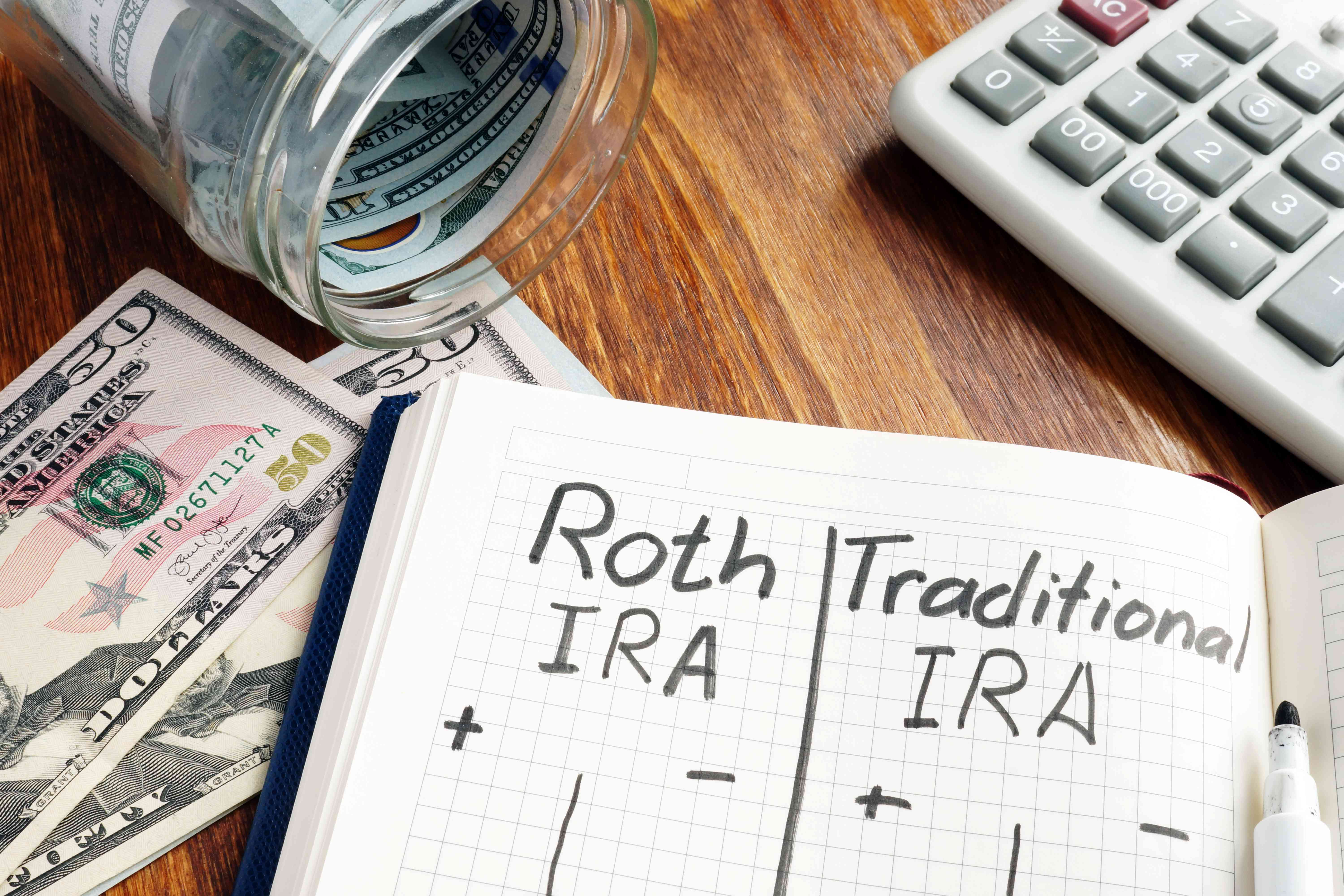 Jar of money with calculator and notebook with Roth IRA and Traditional IRA written down
