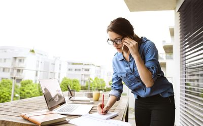 Woman Standing at a Table Working Outdoors With Laptop While on Phone