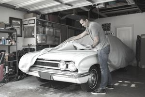 Man uncovering vintage car in garage