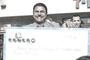 Balbir Atwal, owner of the California 7-Eleven that sold one of the 3 Powerball winning tickets, holds up a $1 million check after received from the California State Lottery, in front of his store on January 14, 2016 in Chino Hills, California.