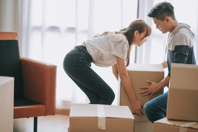 A couple moves boxes in a home or apartment