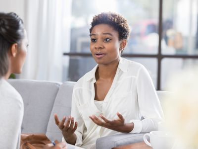 A woman who seems worried or concerned discusses the problem with a woman seated across from her.