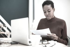person in red sweater sitting in front of computer with paperwork