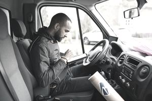 Delivery driver using tablet in truck