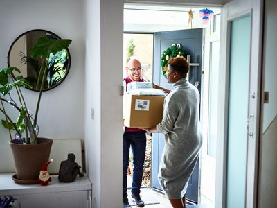 A delivery man hands a box of merchandise to a woman at her front door