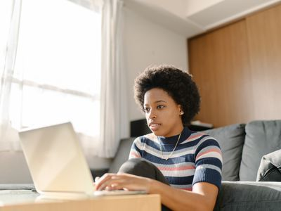 young adult in striped t-shirt doing work from home on computer