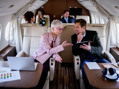 Man and woman talking over tablet on an airplane