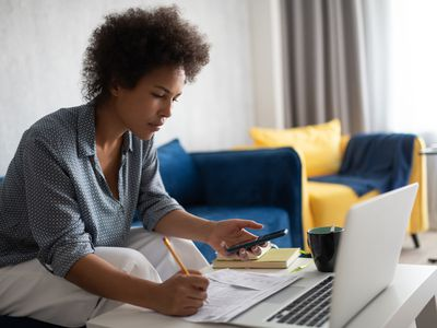 African American female using smartphone to calculate taxes