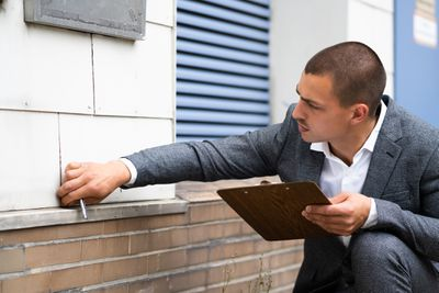 A man with a clipboard inspects the siding shingles on a home.