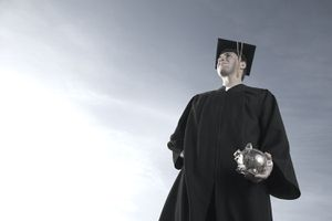 College Graduate in Cap and Gown Holding Clear Piggy Bank Full of Change