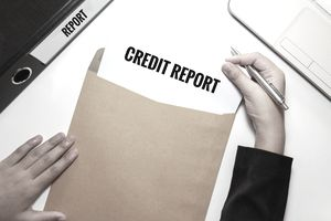 hands taking a paper credit report out of an envelope