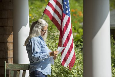 Woman standing on front porch reading a letter with an American flag in the background.