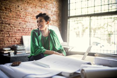 Smiling businesswoman looks over architect blueprints in office