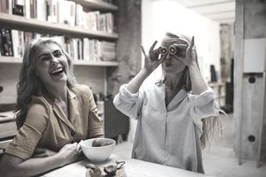 Two women playing with food and laughing